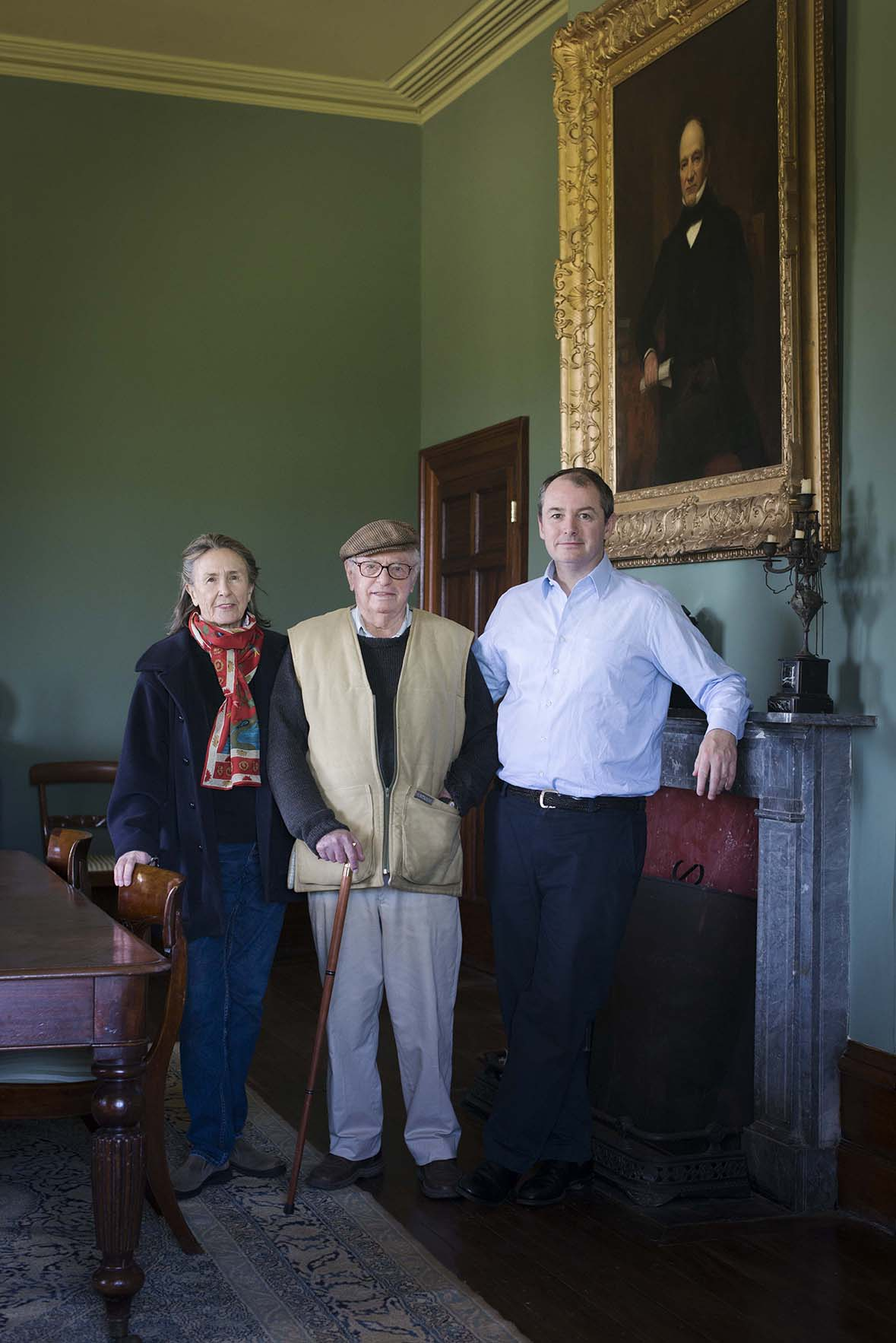Older couple with younger man in front of ornately framed painting over a fireplace in green-painted room.