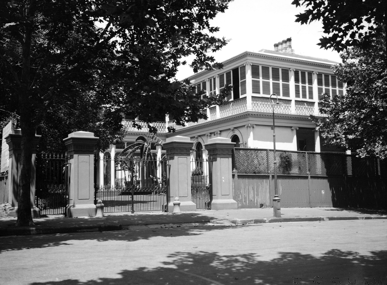 Black and white exterior of house with tree and gates in foreground.