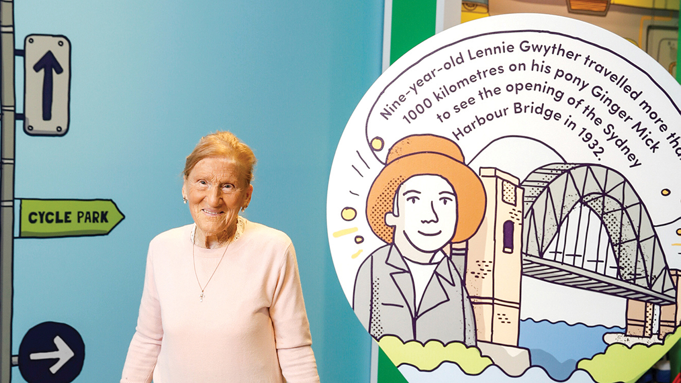 Older woman in front of exhibition display.