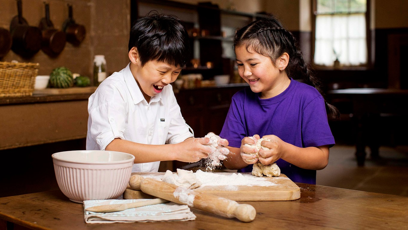 Boy and girl making dough in kitchen