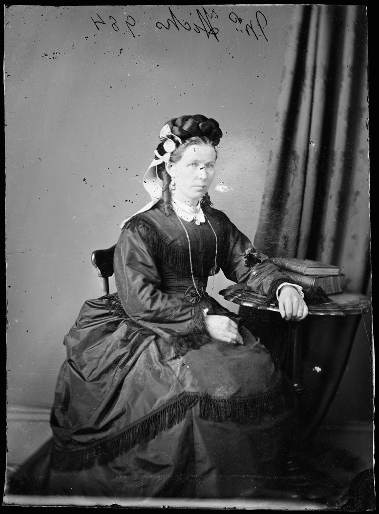 Black and white photo of woman in formal dress seated at table.