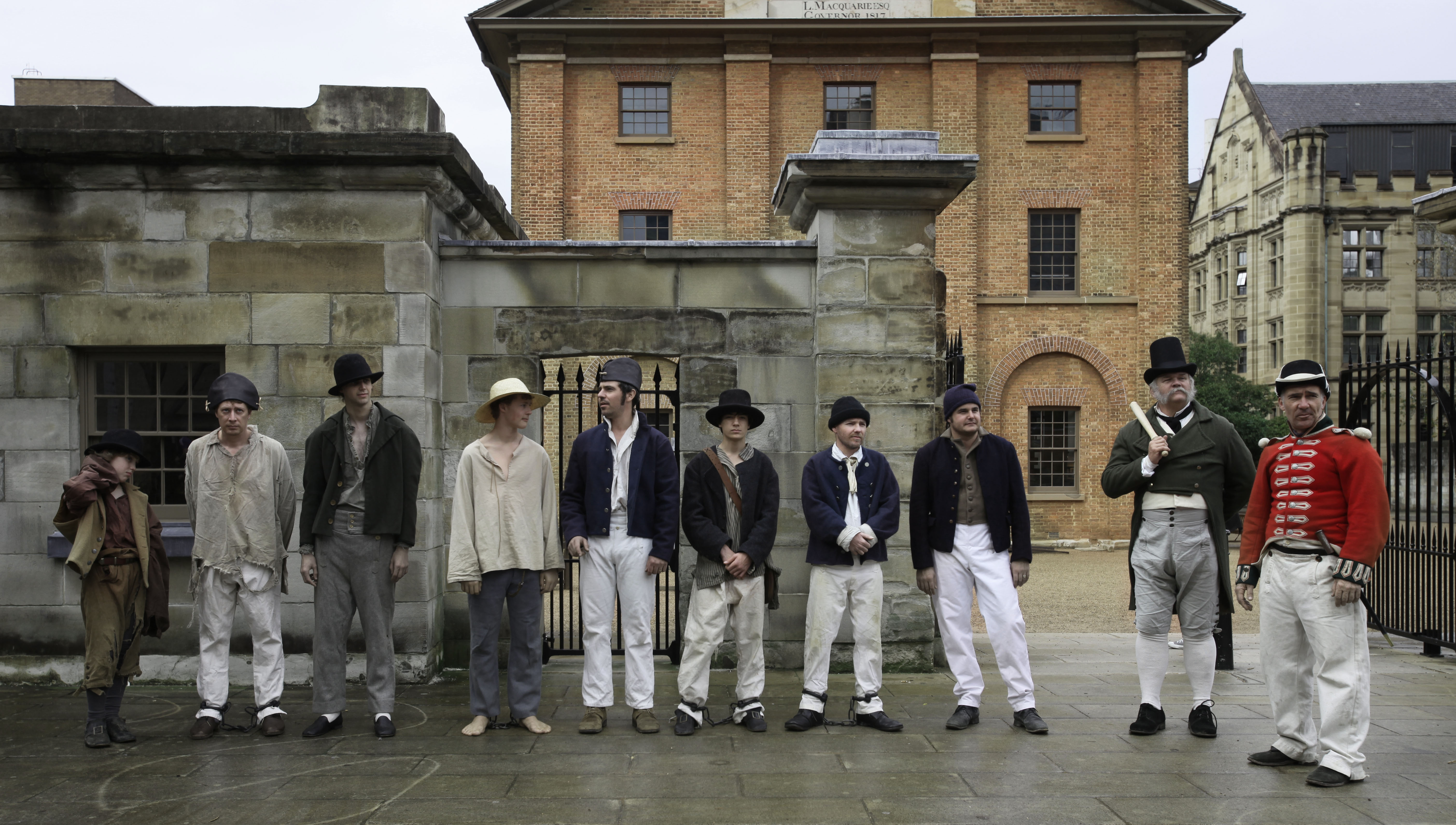 A group of convicts gathers outside the gates to the Hyde Park Barracks. An overseer and a redcoat watch over.