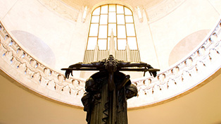 Stark statue of dead soldier with arms outstretched in centre of domed room.