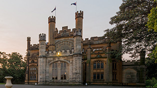 Castlelike facade of sandstone building with flags on top of twin turrets.