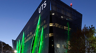 Green lit facade with illuminated letters UTS at top.