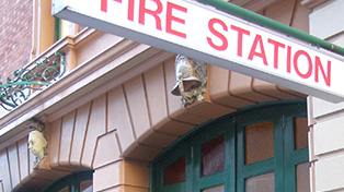 Close up of fire station sign on sandstone facade.