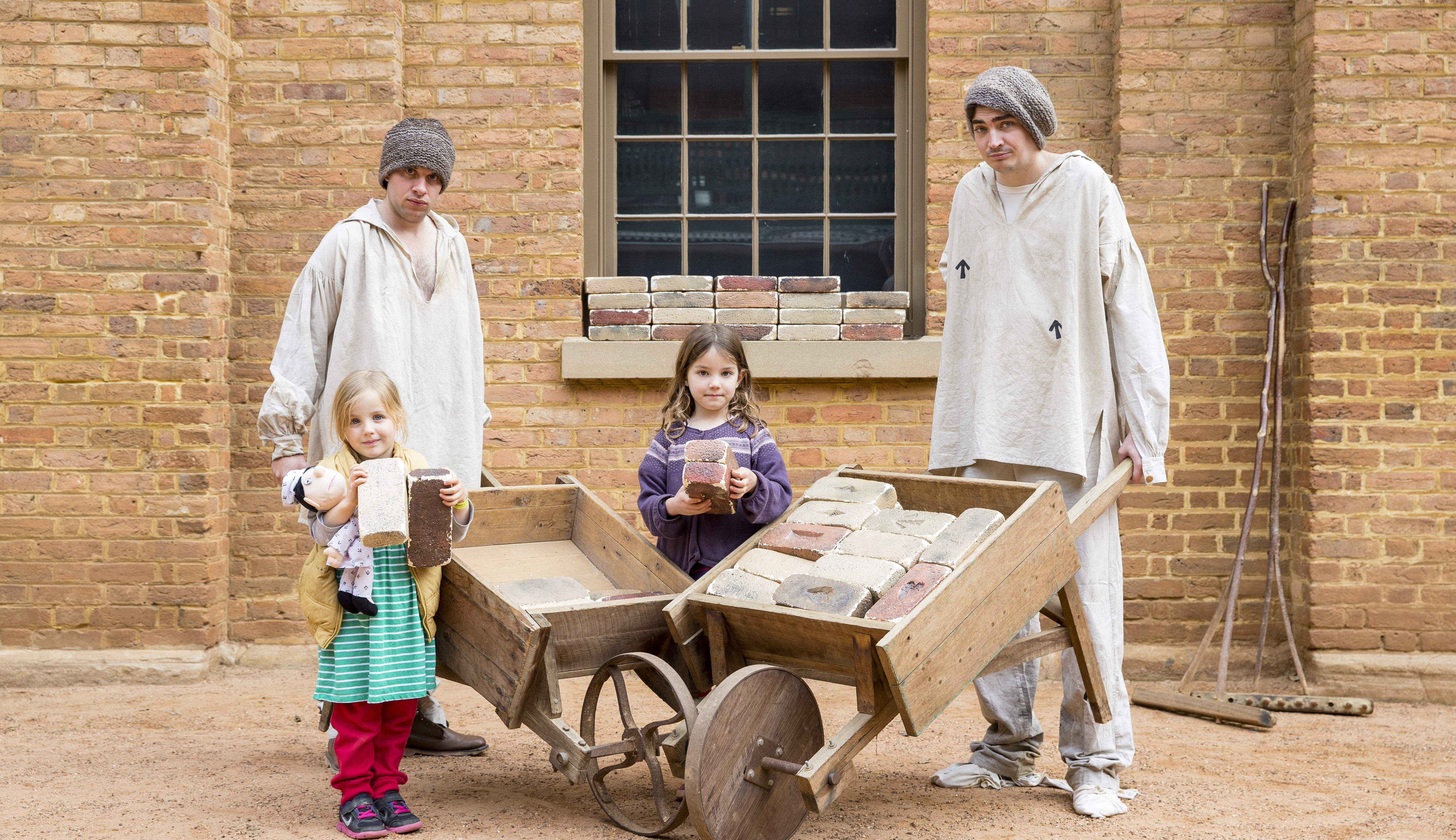 Two actors dressed as convicts holding wheelbarrows, standing with two little kids