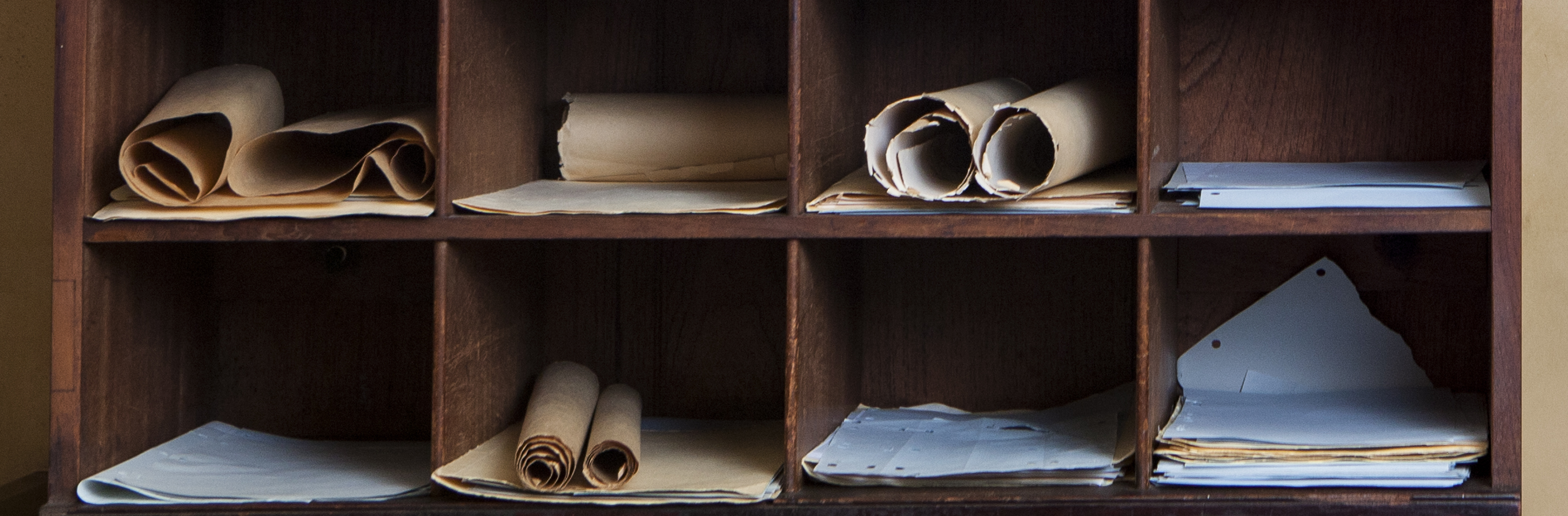 Closeup of old shelving with paper documents and rolled up papers.