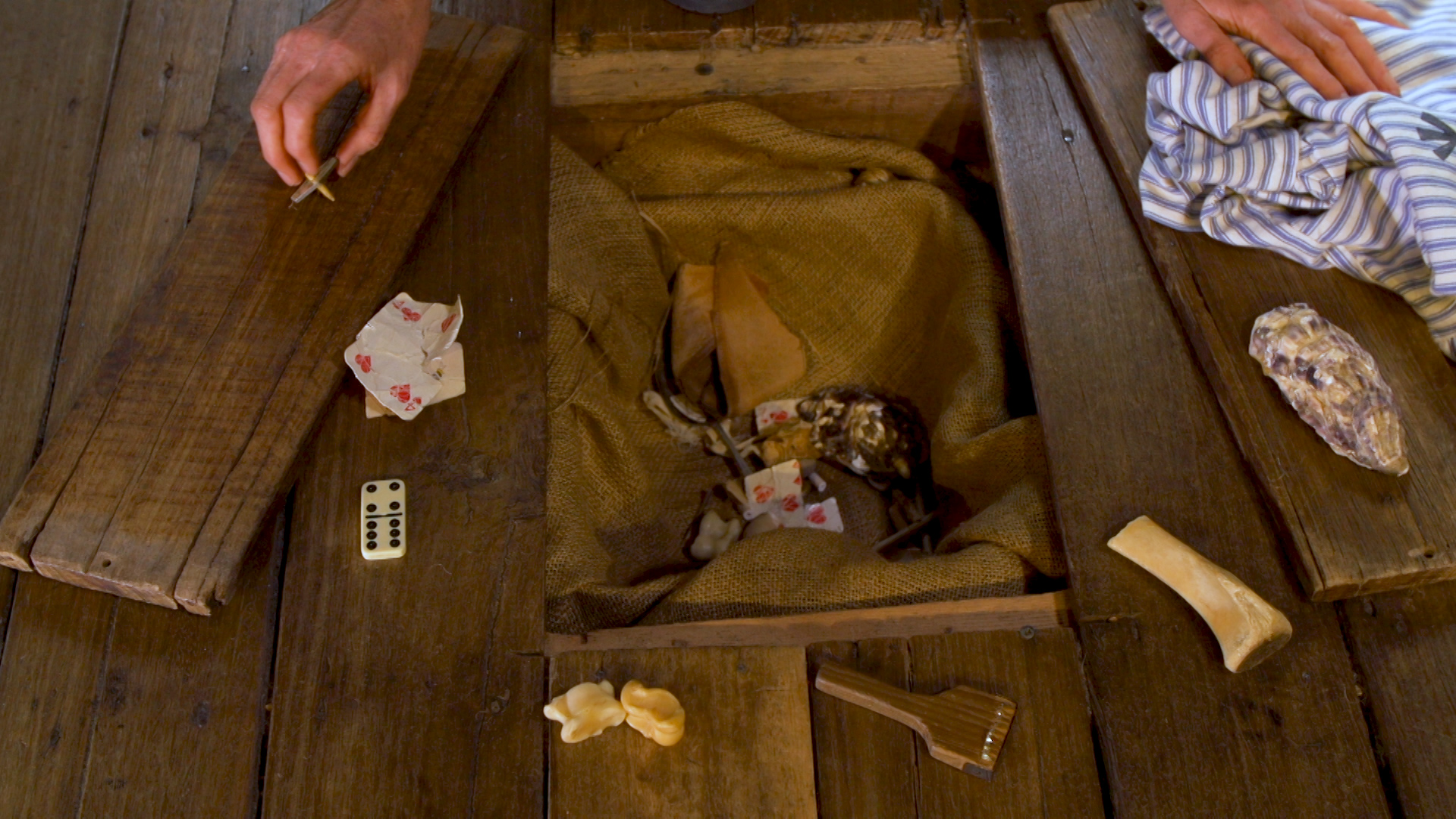 View of opened floorboard space with artefacts.