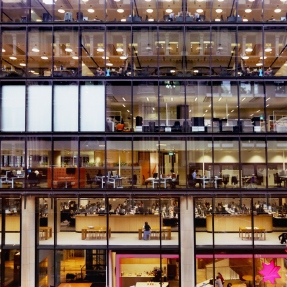 Looking into open plan office spaces through glass-walled building.