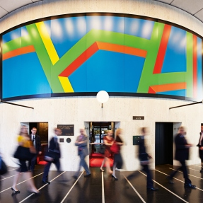 Circular interior space with colourful mural around centre.