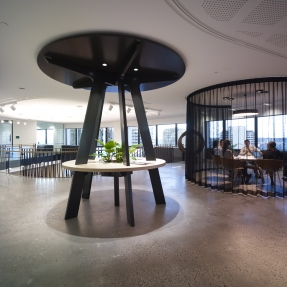 Interior of modern office with circular desk installation in centre of open plan space.