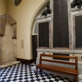 Bench along window in archway with black and white chequer patterned floor.