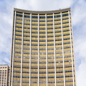 Cropped thumbnail of tall golden building with slightly curved facade and blue sky behind.