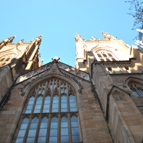 Looking up at tall multiframed window with two towers either side.