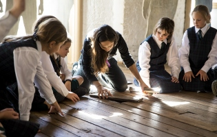 Students and guide looking under a floorboard in Hyde Park Barracks Museum