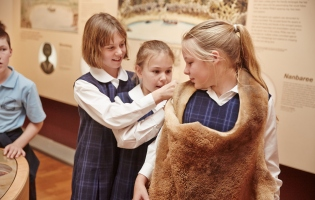 Three girls trying on a skin in exhibition space.