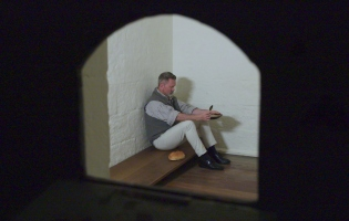 An actor dressed as Captain Moonlite languishes in a police holding cell