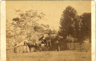 Group in horse-drawn cart outside house.