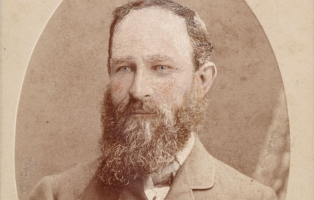 Detail image of a bearded and staunch looking Kenneth Mckenzie.