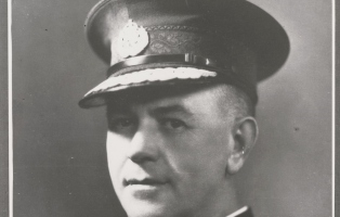 Close cropped portrait of man in police hat.