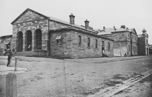 Black and white photograph depicting Phillip Street police station in the 1870s. There are no tall buildings visable and a number of people are sitting on the stairs or on the street.