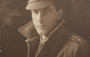 Photo of man in army uniform with coat collar turned up and cap.