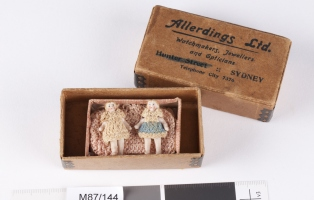 A cardboard box, containing a pair of pink knitted booties with laces, and two female dolls wearing crocheted clothing.
