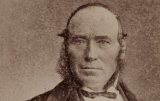 sepia toned close up portrait of man with balding head and bow tie looking straight into camera.