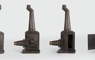 Set of four photos from different angles of metal box with lens and chimney.