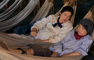 Actors dressed as convicts in hammocks.