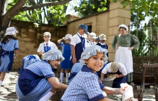 School children wearing convict costumes and doing washing activities with water buckets, scrubbing boards and basins in the oak tree courtyard, during an education program at Elizabeth Farm.