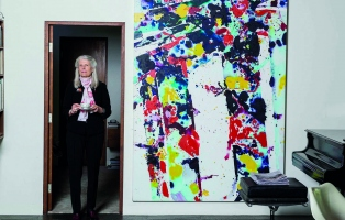 Woman in doorway with painting to her left.