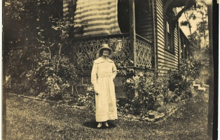 Woman in long white dress and hat standing in garden in front of Meroogal verandah.