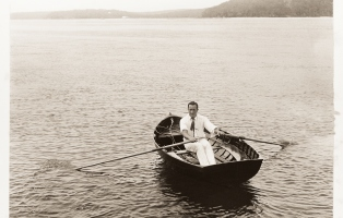 Black and white image of a man dressed in white rowing a dinghy in calm water.