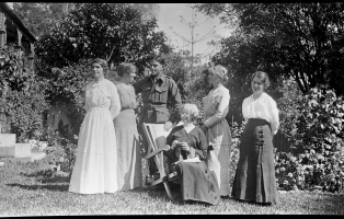 Group of woman standing around older seated woman who is knitting.