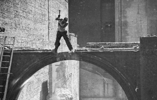black and white image of a worker demolishing a building