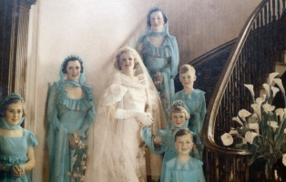 Colourised black and white photo of bridal party on staircase.