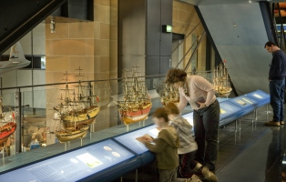 Visitors looking at the first fleet ships. This is a long display of models of the first fleet ships behind a graphic.