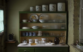 Shelving with tins, crockery and other kitchen items, lit from side by light coming in window.