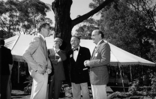 Black and white photograph of four men standing in front of tree in garden.