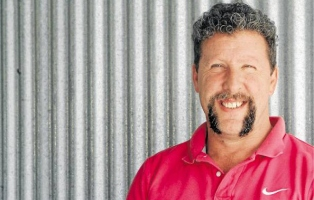 Smiling man in red shirt standing in front of corrugated iron surface.