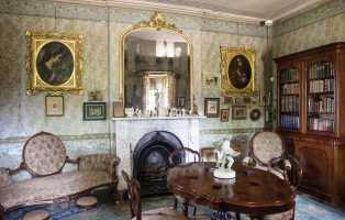 View of the sitting room, showing fireplace, mirror, table, chairs and sofa. Bookcase is in righthand corner.