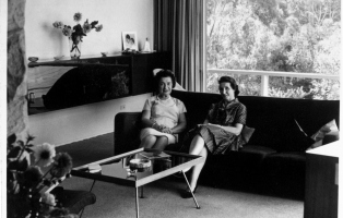 B/W photo showing two women sitting in couch in living room with coffee table in front, sideboard beside them and large window and curtains, with trees visible outside.