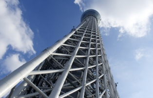 Looking upwards through the white tubular geometric scaffolding structure around the central column of the Toyko Skytree against a blue sky