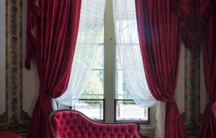 Deep red chaise longue in front of window framed with matching curtains.