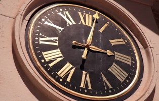 Close up view of the face of the Hyde Park Barracks clock in bright dunlight. The time is 2 minutes past 3.