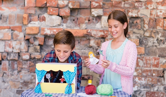 Two children making and playing with puppets
