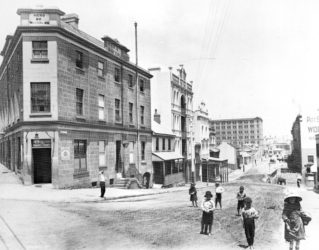 Black and white view of street with sandstone pub on the corner and children playing on the street.