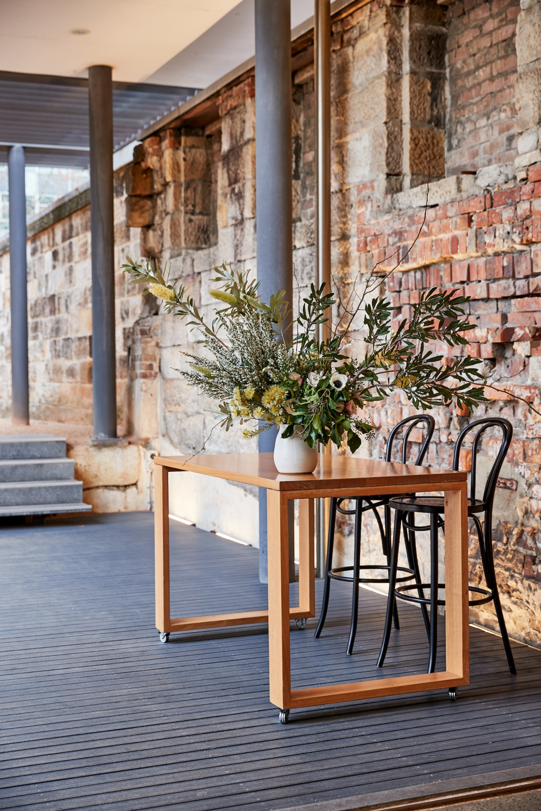 Outdoor space with cover, with floral arrangements set up on wooden table.
